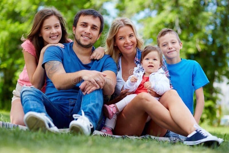 Lycklig familj som vilar i sommar royaltyfri foto