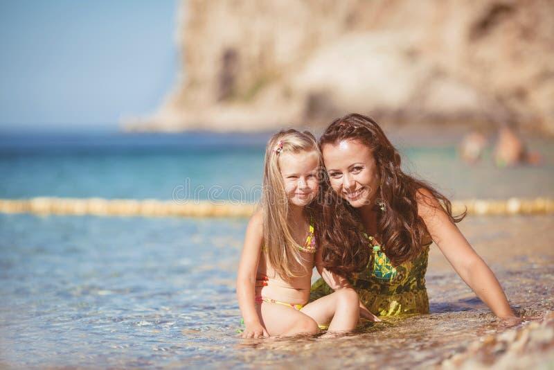 Lycklig familj som vilar på stranden i sommar arkivfoton