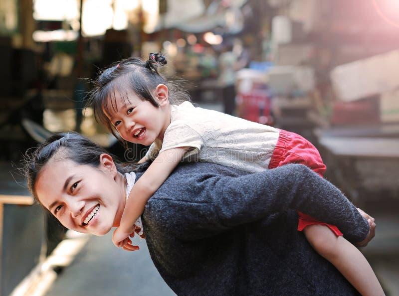 Lycklig familj, stående av den gulliga liten flickaridningen på moderbaksida i Bangkok Thailand arkivbilder