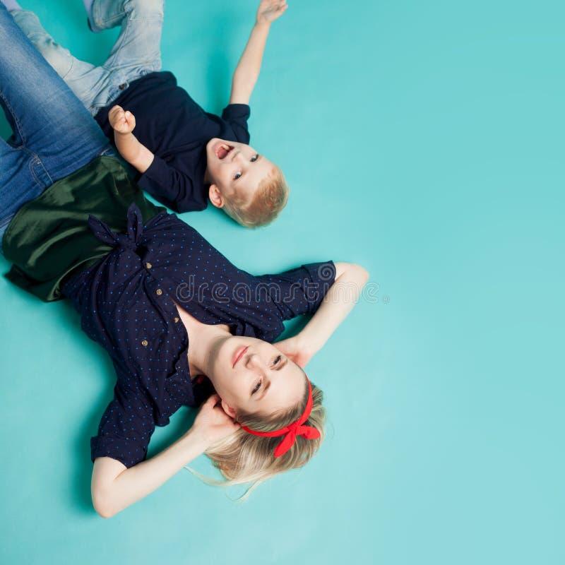 lycklig familj Ung härlig blond kvinna med den roliga sonen Lögn sikten uppifrån fotografering för bildbyråer