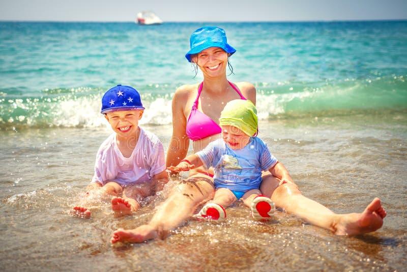 Lycklig familjbadning i havet Le modern med hennes son och dotter på stranden Sommarsemester på havsstranden royaltyfria bilder