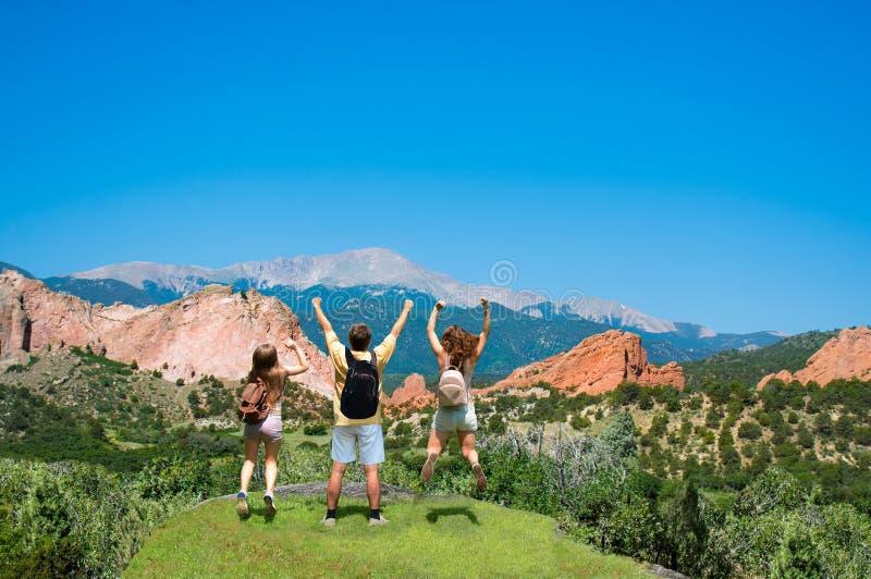 Lycklig familjbanhoppning med lyftta händer på semestern som fotvandrar tur arkivbild
