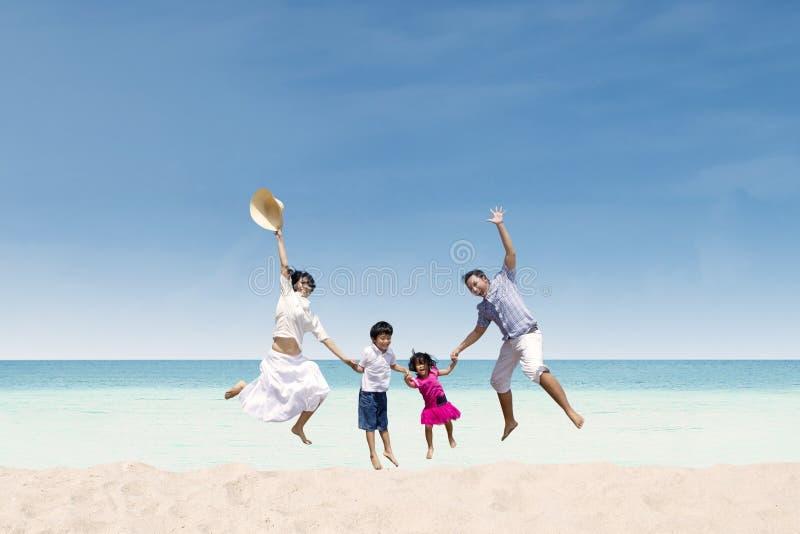 Lycklig familjbanhoppning på stranden arkivbild