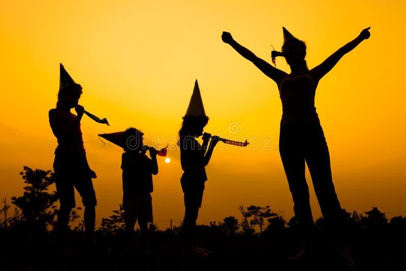 Lycklig familjdans på vägen på solnedgångtiden royaltyfri bild