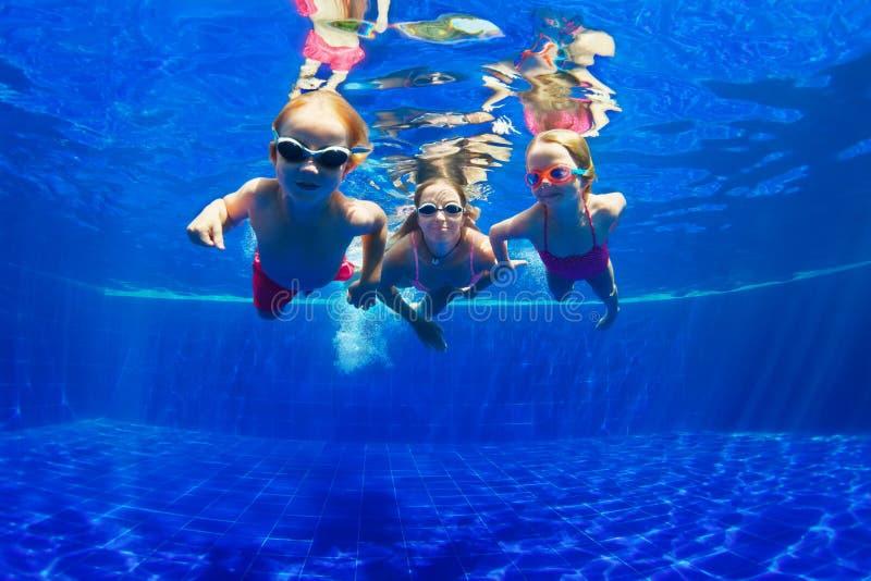 Lycklig familjdyk som är undervattens- i simbassäng royaltyfri bild