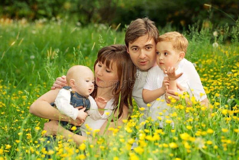 Lycklig familjfader, moder och söner som kopplar av i parkera royaltyfria foton