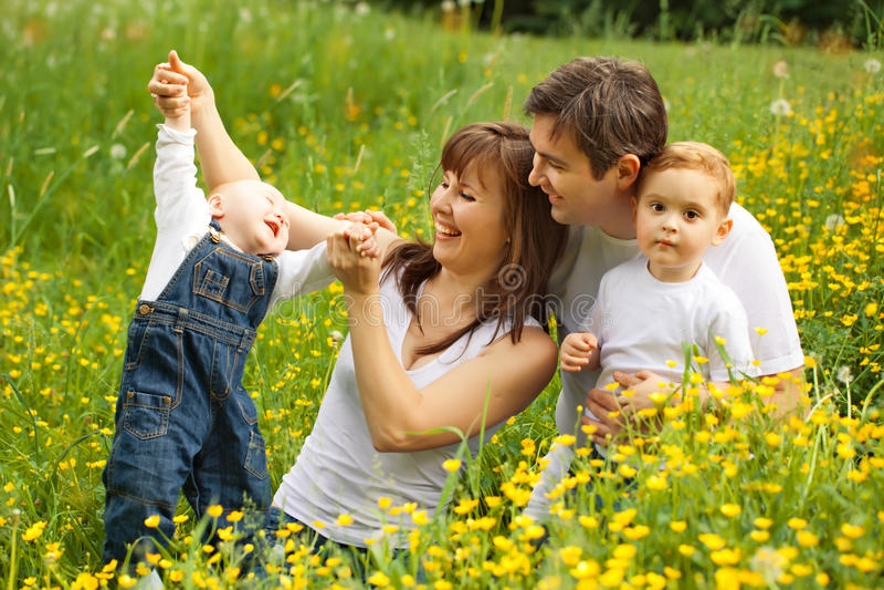 Lycklig familjfader? moder och söner som kopplar av i parkera fotografering för bildbyråer