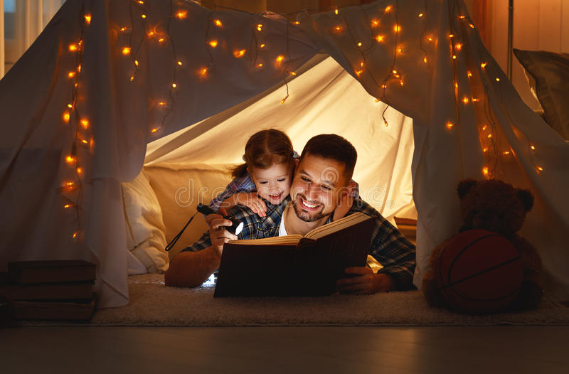 Lycklig familjfader och barndotter som läser en bok i tält royaltyfria foton