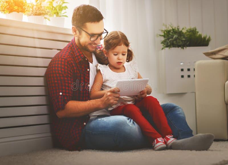 Lycklig familjfader och dotter som spelar med minnestavladatoren royaltyfri foto