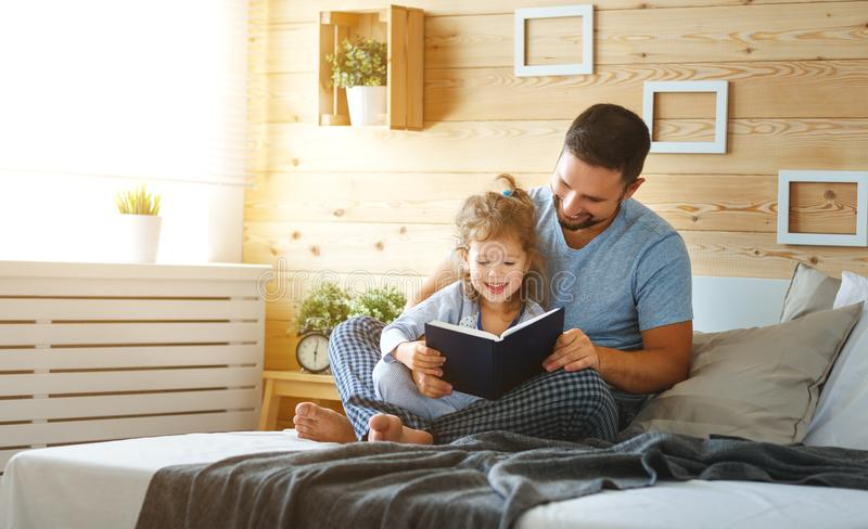 Lycklig familjfader och dotterläsebok i säng royaltyfria bilder