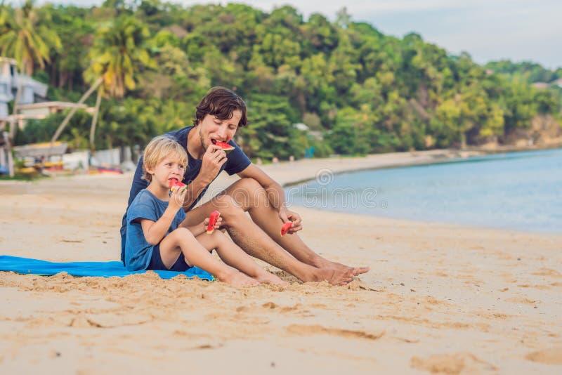 Lycklig familjfader och son som äter en vattenmelon på stranden Barn äter sund mat royaltyfria bilder