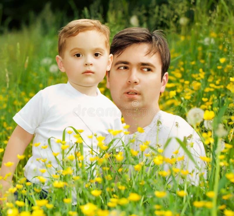Lycklig familjfader och son som kopplar av i parkera arkivbilder