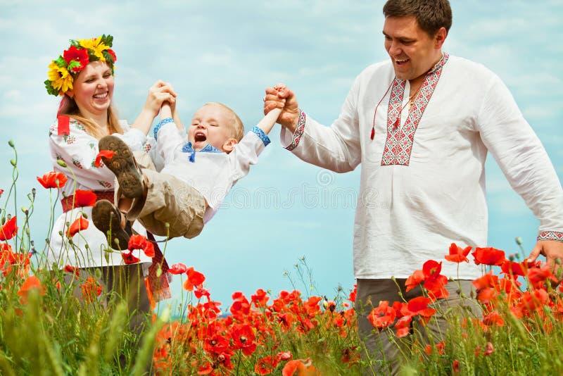 Lycklig familjfritid på vallmofält arkivfoto
