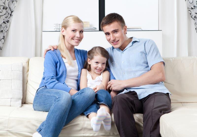 Lycklig familjkram varje annan på sofaen fotografering för bildbyråer