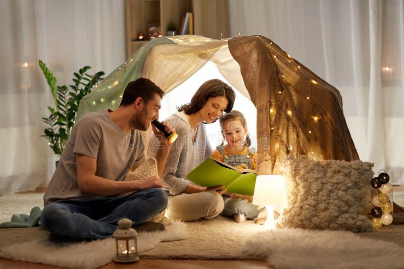 Lycklig familjläsebok i ungetält hemma royaltyfri fotografi