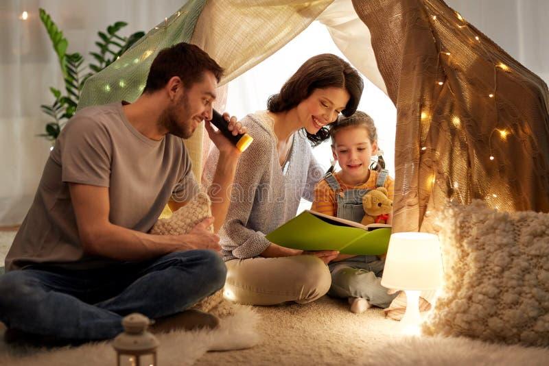 Lycklig familjläsebok i ungetält hemma royaltyfri bild