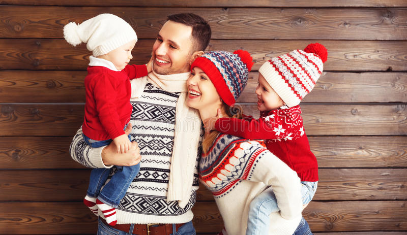 Lycklig familjmoder, fader och barn i vinterhattar på woode arkivbilder