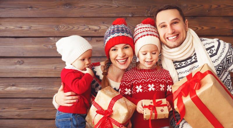 Lycklig familjmoder, fader och barn med julgåvor på royaltyfri fotografi