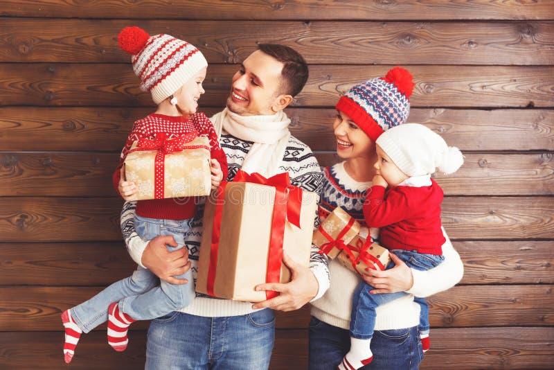 Lycklig familjmoder, fader och barn med julgåvor på arkivbild