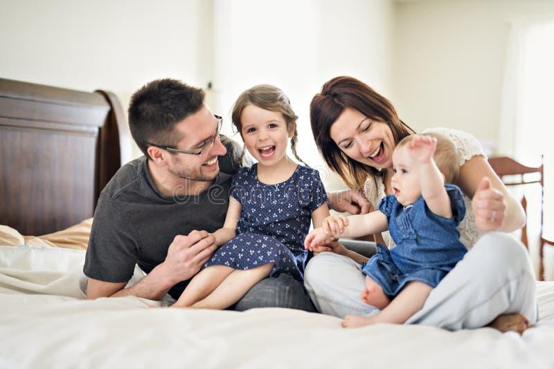 Lycklig familjmoder, fader och två barn hemma i säng arkivfoton