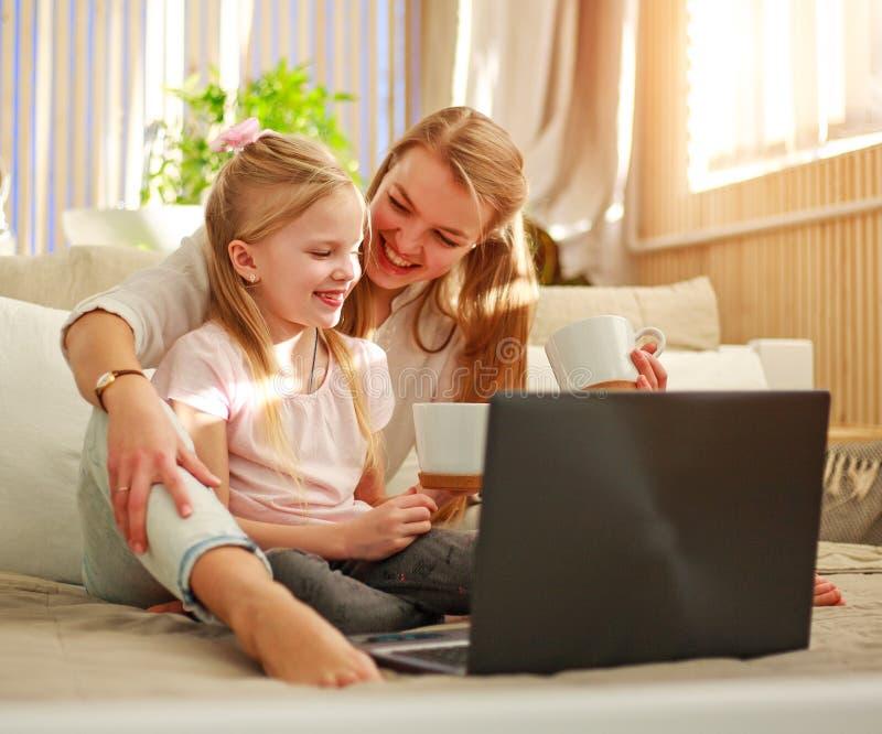 Lycklig familjmoder med dottern som hemma använder datorbärbara datorn, modern livsstil royaltyfri bild