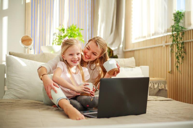 Lycklig familjmoder med dottern som hemma använder datorbärbara datorn, modern livsstil royaltyfria bilder