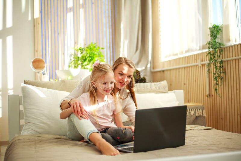 Lycklig familjmoder med dottern som hemma använder datorbärbara datorn, modern livsstil fotografering för bildbyråer
