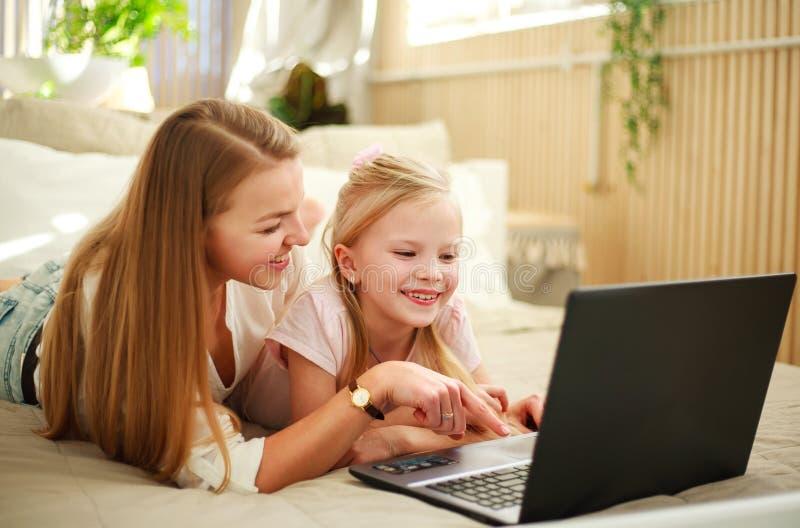 Lycklig familjmoder med dottern som hemma använder datorbärbara datorn, modern livsstil royaltyfri fotografi