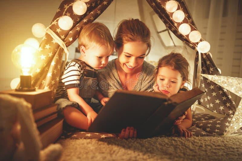 Lycklig familjmoder och barn som läser en bok i tält på hom royaltyfri bild