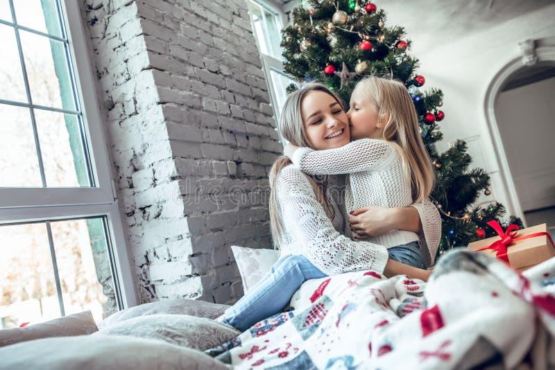 Lycklig familjmoder och barndotter på julmorgon på julgranen med gåvor royaltyfri bild