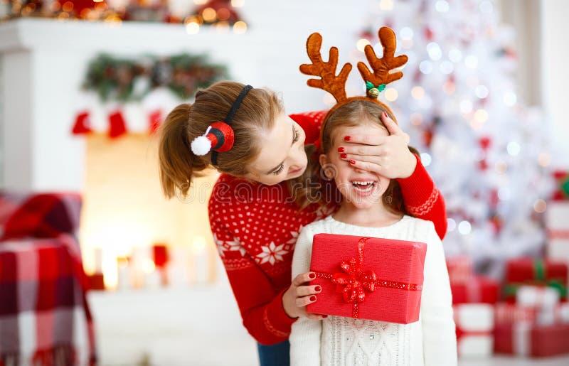 Lycklig familjmoder och dotter som ger julgåvan arkivbild