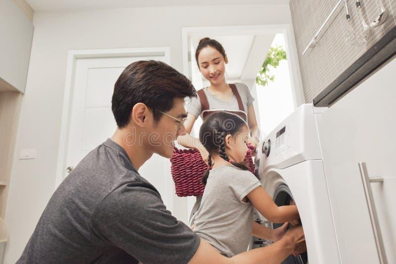 Lycklig familjpäfyllningskläder in i tvagningmaskinen i hem arkivfoto