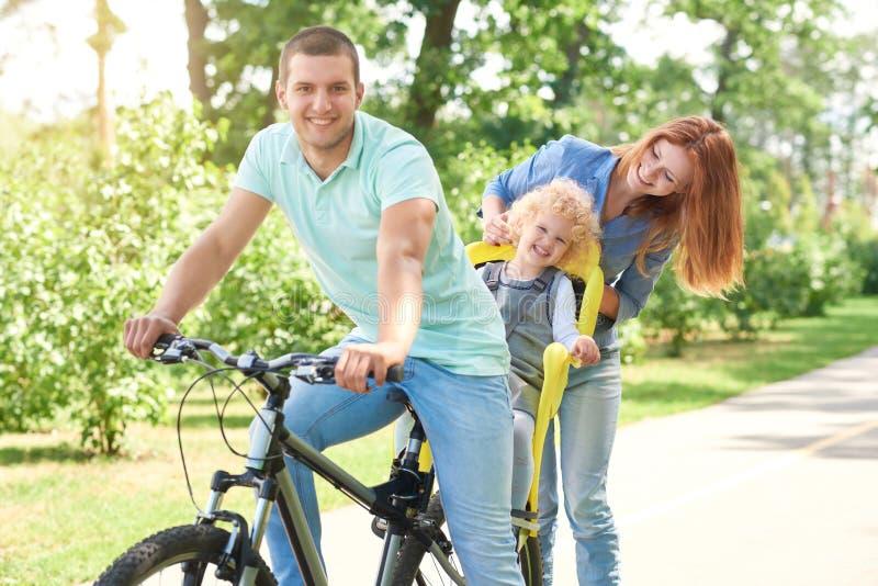 Lycklig familjridningcykel på parkera royaltyfri bild