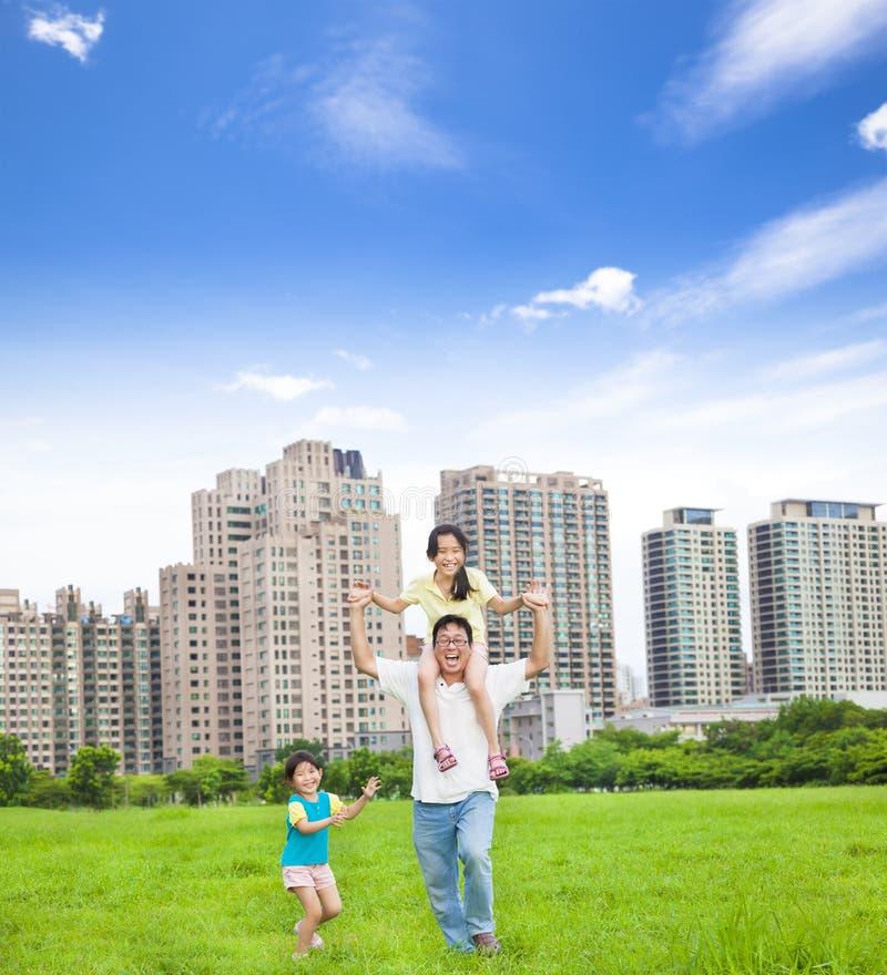 Lycklig familjspring i staden parkerar arkivfoto