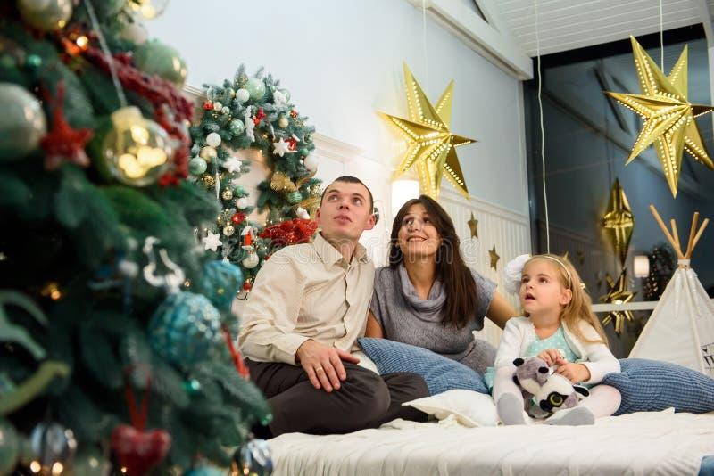 Lycklig familjstående på jul, modern, fadern och barnet som hemma sitter på säng, chritmasgarnering runt om dem arkivbilder