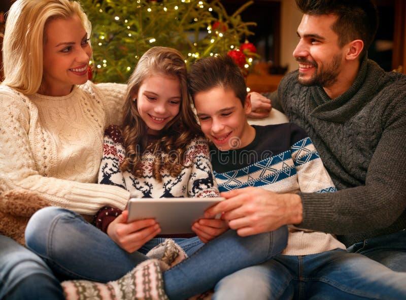 Lycklig familjtid - familj som använder den digitala minnestavlan på julhol royaltyfri foto