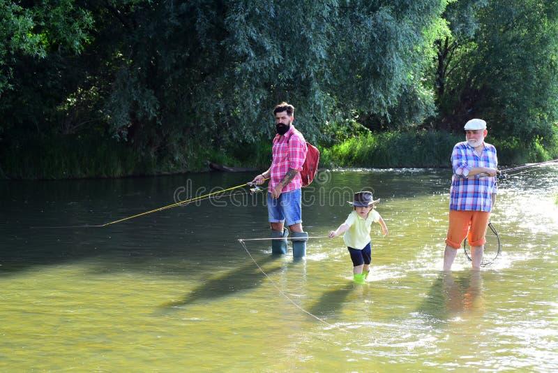 Lycklig farfar, fader och sonson med metspön på flodhytten fiska fluga Pys på en sjö med hans fotografering för bildbyråer