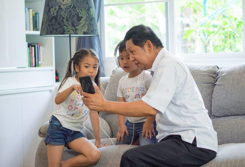 lycklig farfar med ungar som använder smartphonen som tillsammans delar headphonen för att lyssna till musik och att tycka om och royaltyfria foton