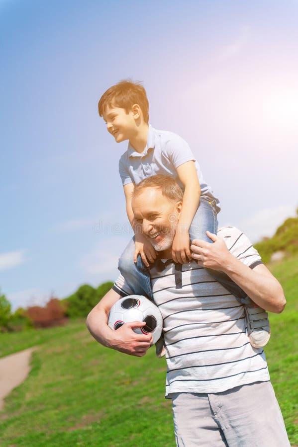 Lycklig farfar och barn som tillsammans underhåller royaltyfria bilder