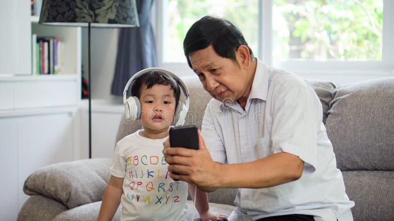 lycklig farfar och sonson som delar smartphonen som lyssnar tillsammans till musik med headphonen som tycker om på soffan eller s royaltyfri fotografi