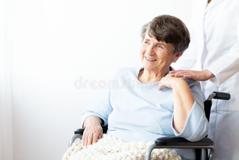Lycklig farmor i en rullstol och en anhörigvårdare som stöttar henne royaltyfri foto