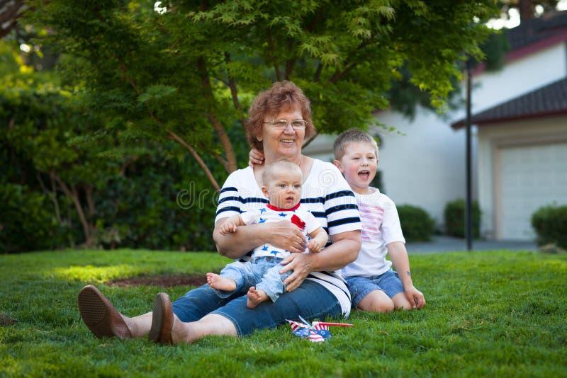 Lycklig farmor med två pyser som firar Juli 4th royaltyfri foto