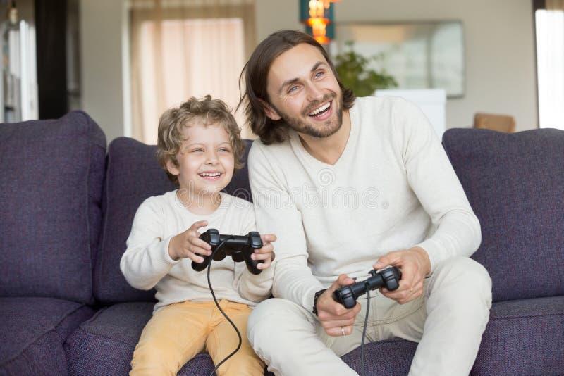 Lycklig farsa som har gyckel som skrattar spela videospel med sonen royaltyfria bilder