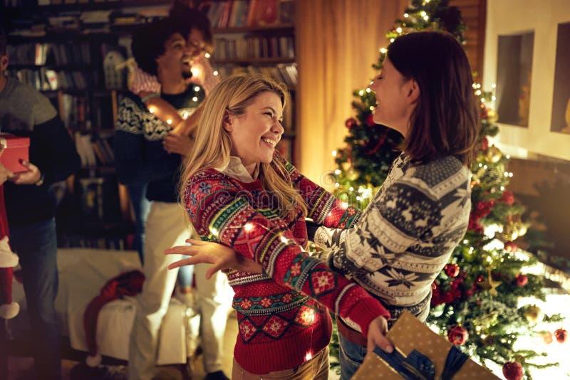 Lycklig ferie - överraskning för vän med gåva på jul royaltyfri bild