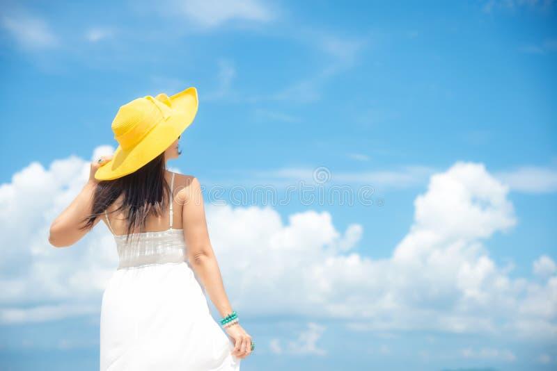 Lycklig ferie och sommar Danar den bärande vita klänningen för den asiatiska kvinnan och den gula stora hatten sommar royaltyfria foton