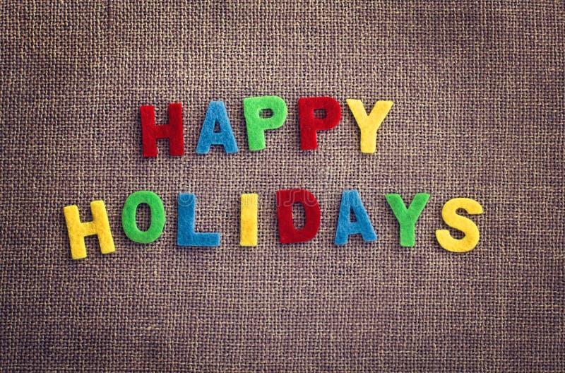 Lycklig feriegiftcard som göras av flerfärgade bokstäver på kontrastlintextilen arkivbilder