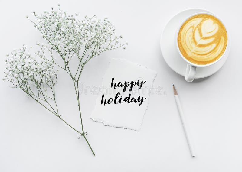 Lycklig ferietext med anmärkningspapper, blommabuketten och kaffekoppen arkivbilder