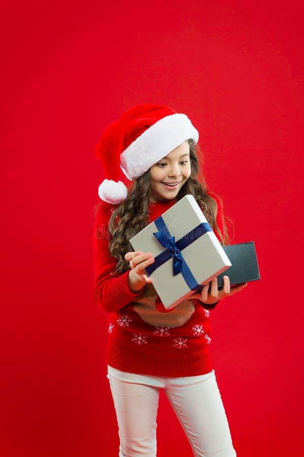 lycklig ferievinter liten flicka Liten flickabarn i santa den röda hatten Gåva för Xmas Barndom shoppa för jul arkivfoton