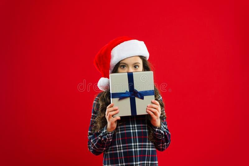 lycklig ferievinter liten flicka Parti för nytt år Santa Claus unge Liten flickabarn i santa den röda hatten Gåva för Xmas arkivfoto