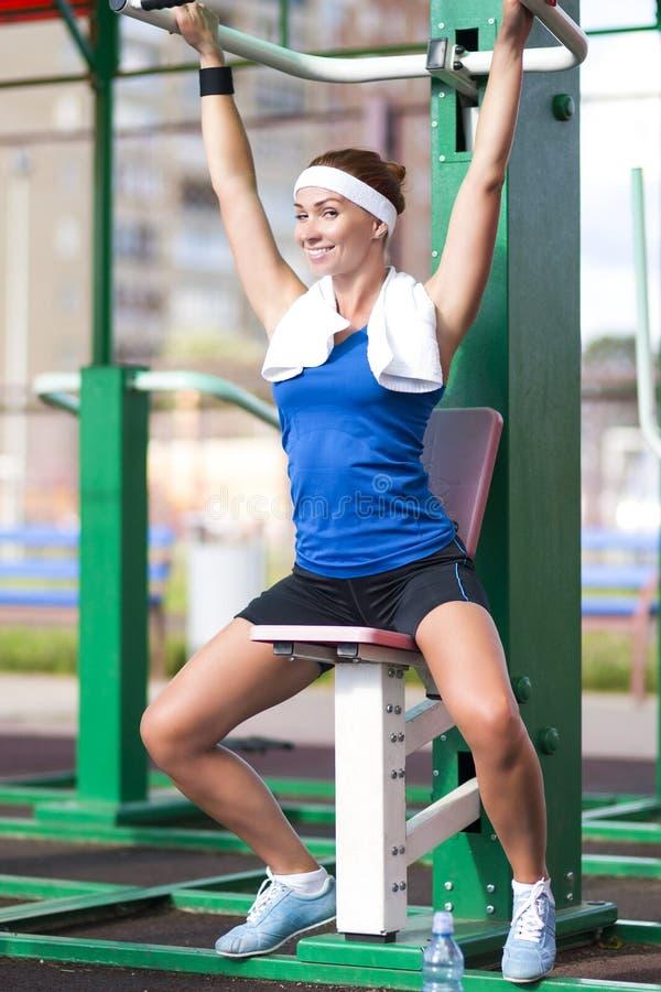 Lycklig flörta Caucasian kvinnlig idrottsman nen i att ha hennes vilotid under utbildning på bukgenomkörarehjälpmedlet utomhus royaltyfria foton